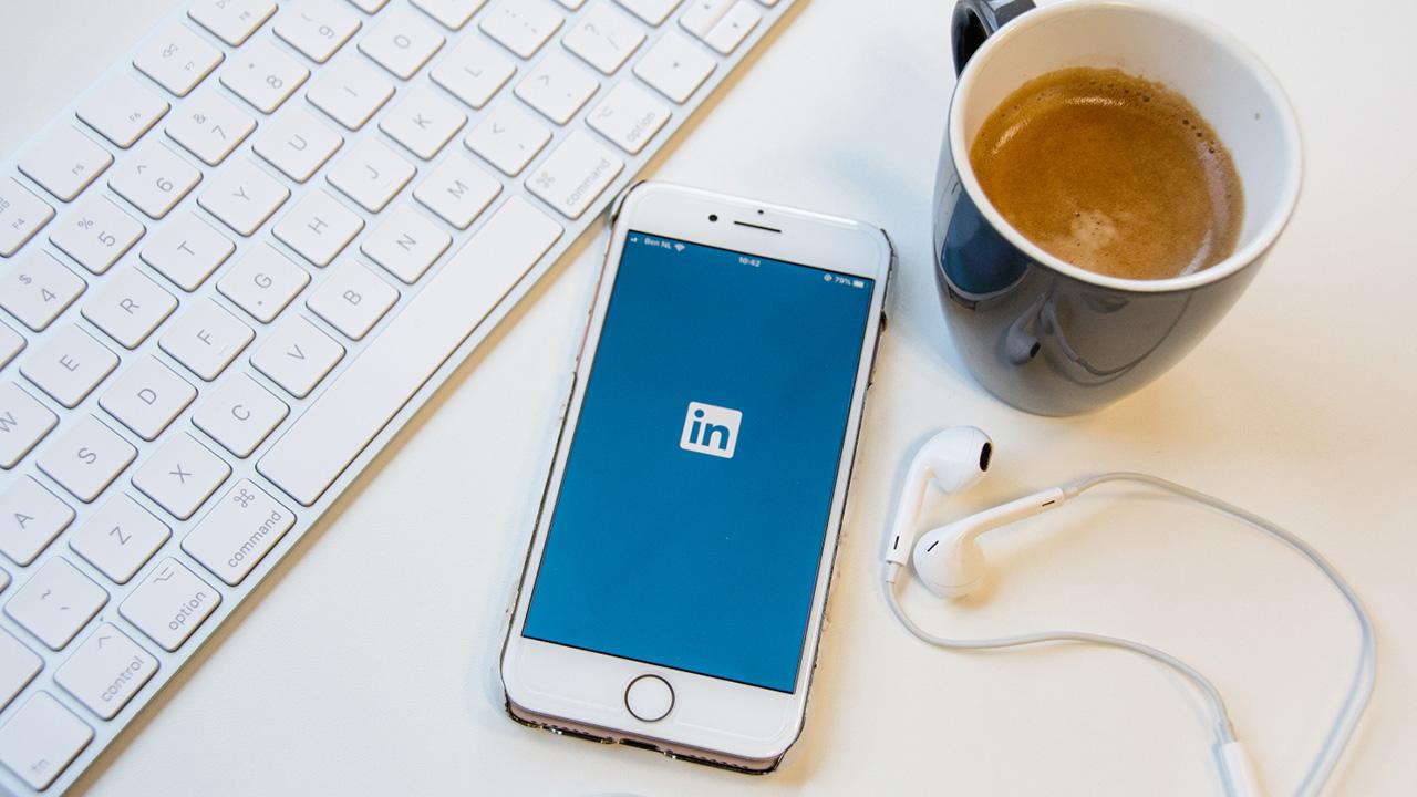 Telefoon naast toetsenbord op bureau met LinkedIn geopend.